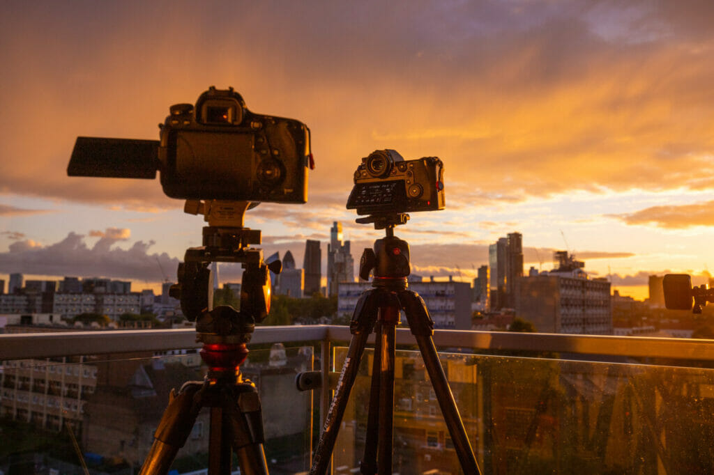 A silhouetted image of two cameras at sunset with the skyline of the city of london in the back